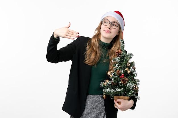 흰색 책상 새 해 크리스마스 장난감에 크리스마스 트리를 들고 전면보기 젊은 여성