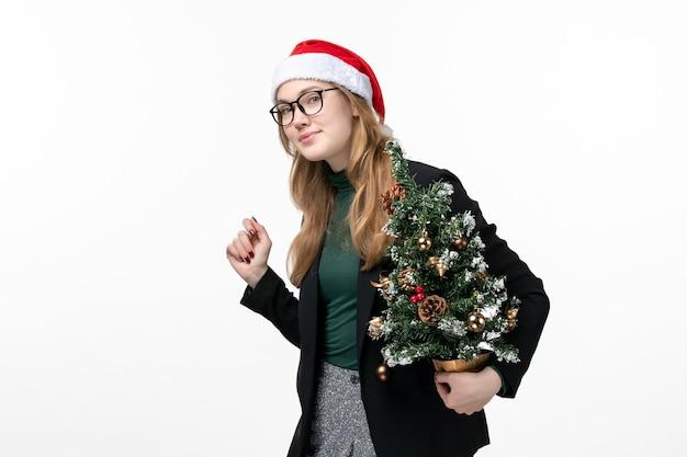 흰색 책상 장난감 새 해 크리스마스에 크리스마스 트리를 들고 전면보기 젊은 여성