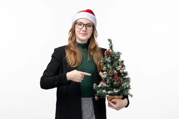 흰색 바닥 새 해 크리스마스 장난감에 크리스마스 트리를 들고 전면보기 젊은 여성