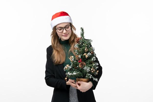 흰 벽 새 해 크리스마스 장난감에 크리스마스 트리를 들고 전면보기 젊은 여성