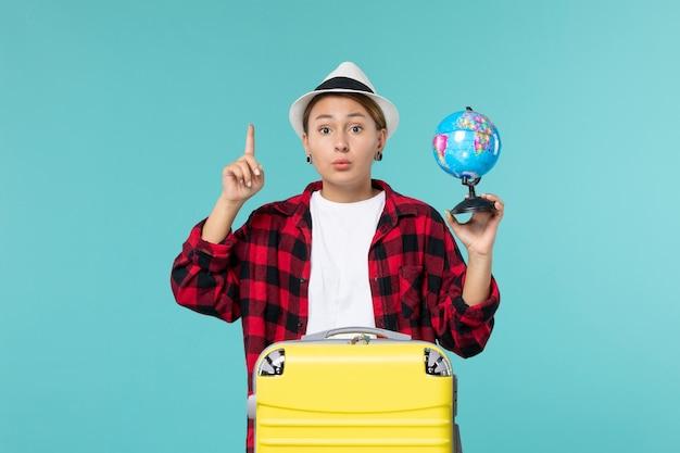 小さな地球儀を保持し、青い机の上で旅行の準備をしている正面図若い女性