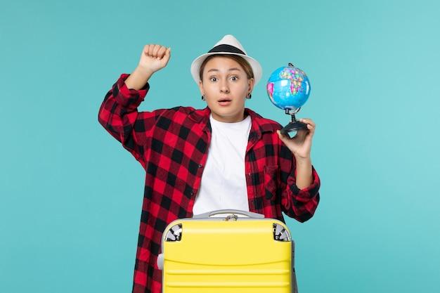 小さな地球を保持し、青い空間での旅行の準備をしている正面図若い女性