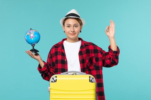 Giovane femmina di vista frontale che tiene piccolo globo sullo spazio azzurro