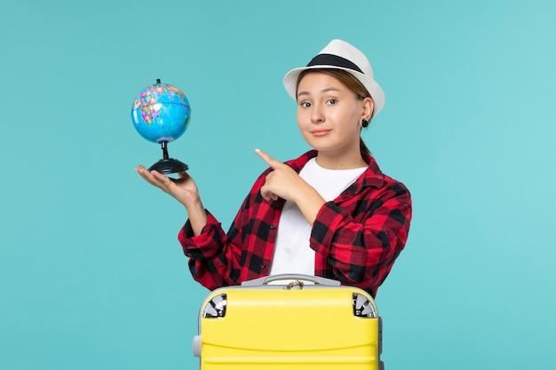 Вид спереди молодая женщина держит маленький глобус на синем пространстве