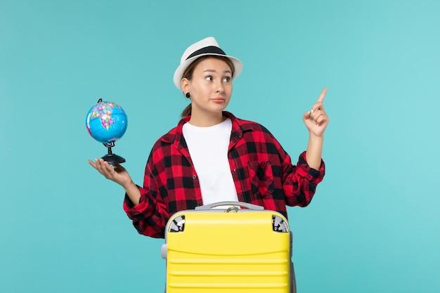 Вид спереди молодая женщина, держащая маленький глобус на синем столе