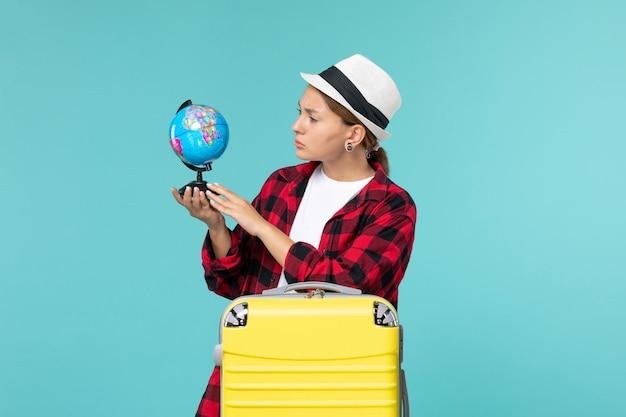 青いスペースに小さな地球を保持している正面図若い女性