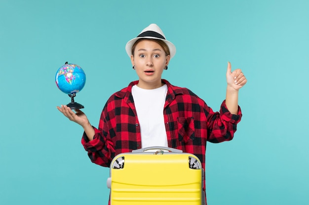 Вид спереди молодая женщина держит маленький глобус на голубом пространстве