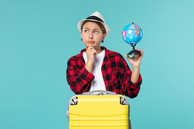 Giovane femmina di vista frontale che tiene piccolo globo e si prepara per il viaggio nello spazio blu