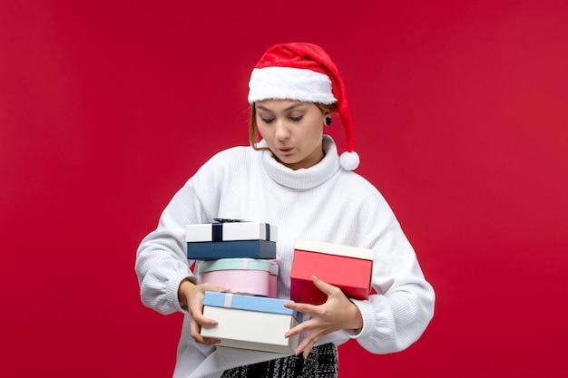 明るい赤の背景に新年のプレゼントを保持している正面図若い女性