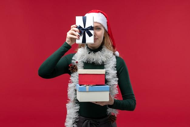 Вид спереди молодая женщина держит новогодние подарки на красном фоне