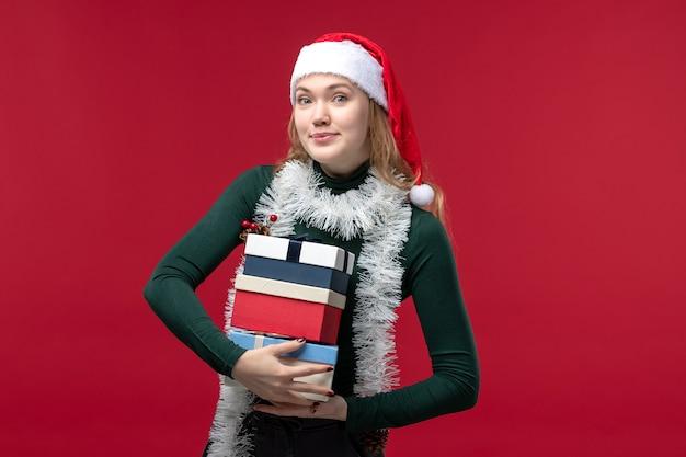 正面図赤い背景に新年のプレゼントを保持している若い女性