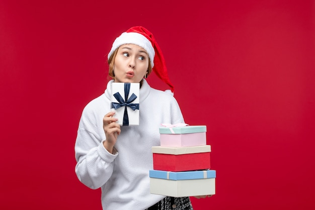 Вид спереди молодая женщина держит новогодние подарки на красном столе