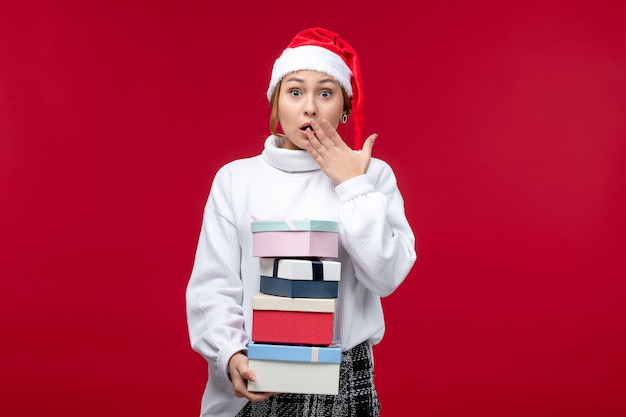 Front view young female holding new year presents on a red background