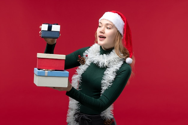 Front view young female holding new year presents on red background
