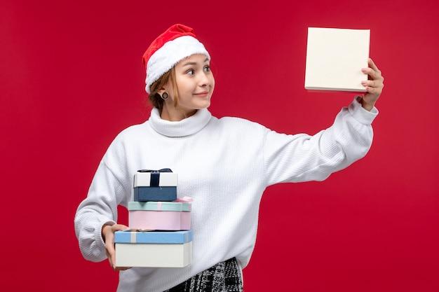 La giovane femmina di vista frontale che tiene i regali del nuovo anno sul rosso di natale di festa del pavimento rosso