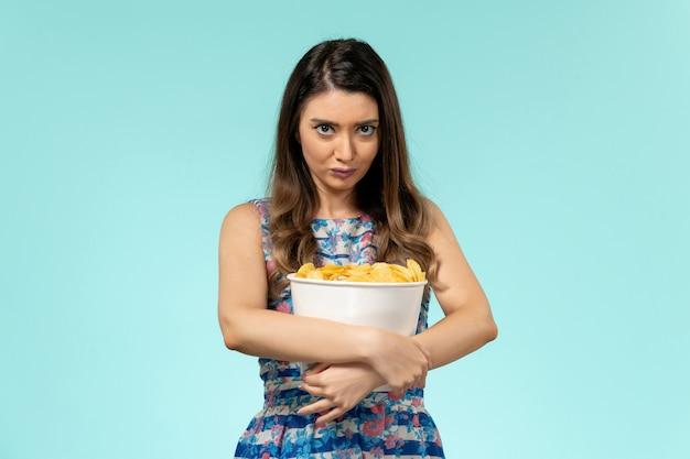 Pacchetto femminile giovane della tenuta di vista frontale con i chip sullo scrittorio blu