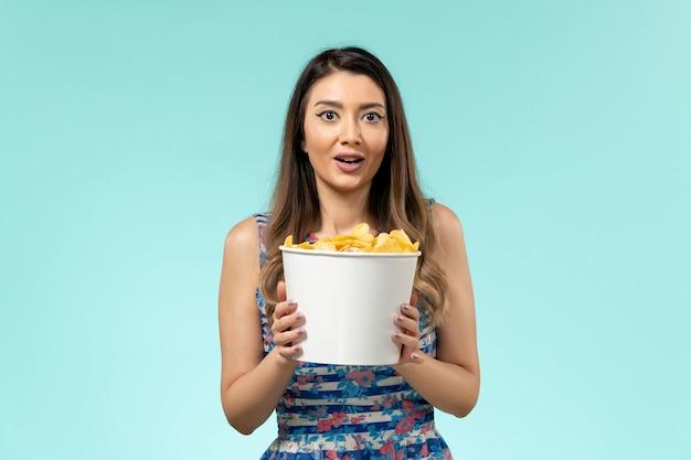 Pacchetto femminile giovane della tenuta di vista frontale con i chip sulla superficie blu