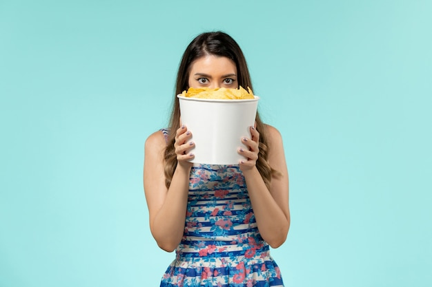 Front view young female holding package with chips on blue surface