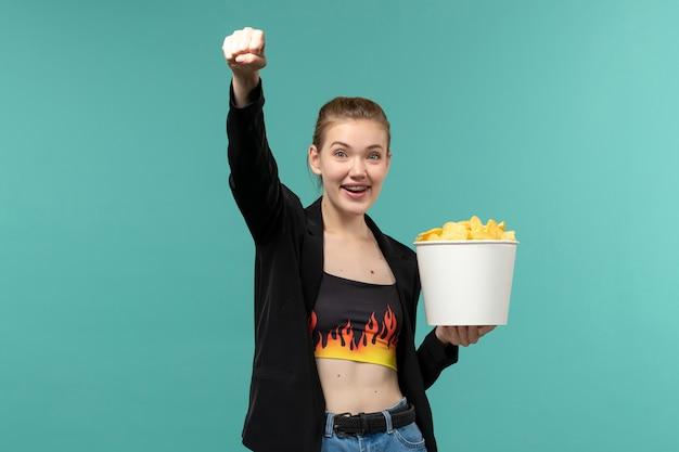 Pacchetto della holding della giovane femmina di vista frontale con patatine fritte e guardare film sulla superficie blu