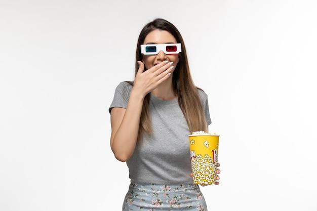 ポップコーンを保持し、明るい白い表面にdサングラスで映画を見ている若い女性の正面図