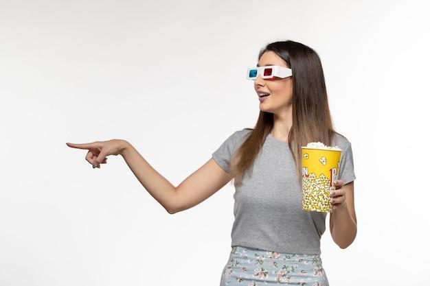 ポップコーンを保持し、白い表面にdサングラスで映画を見ている若い女性の正面図