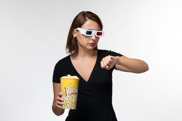 Vista frontale giovane femmina che tiene popcorn in occhiali da sole d guardando il polso sulla superficie bianca