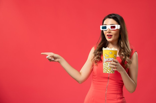 Front view young female holding popcorn in d sunglasses on red desk