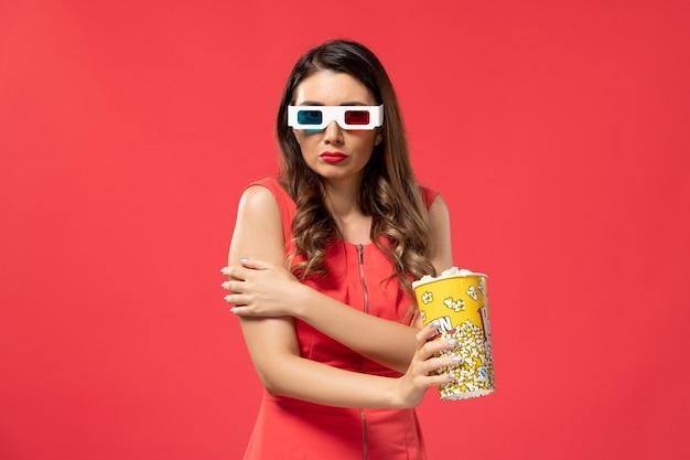 Vista frontale giovane femmina che tiene popcorn in occhiali da sole d sulla superficie rossa