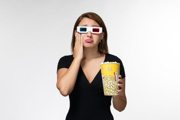 Vista frontale giovane femmina che tiene popcorn in occhiali da sole d guardando film e piangendo sulla superficie bianca