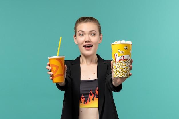 Вид спереди молодая женщина держит попкорн и смотрит фильм на синей поверхности