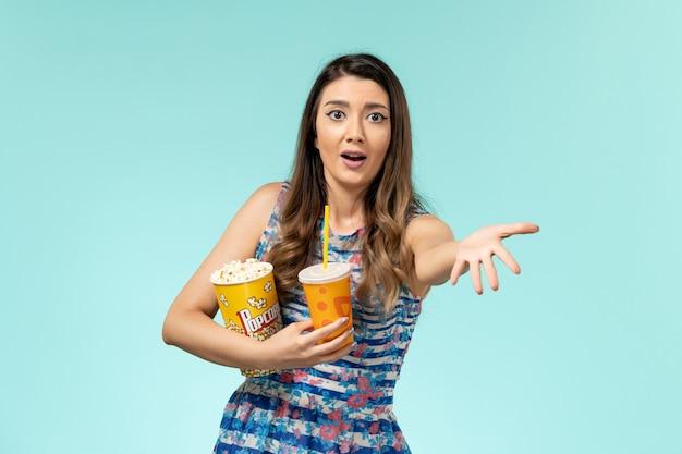 Vista frontale giovane donna che tiene popcorn e bevanda sulla superficie blu