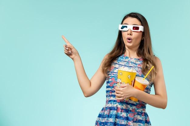 Popcorn e bevanda della tenuta della giovane femmina di vista frontale in occhiali da sole di d sullo scrittorio blu