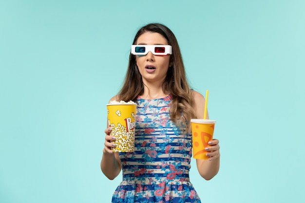 Vista frontale giovane femmina che tiene popcorn e bevanda in occhiali da sole d sulla superficie azzurra