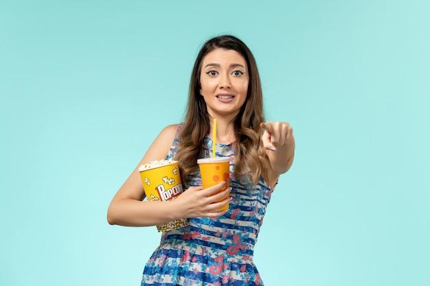 Vista frontale giovane femmina che tiene popcorn e bevanda sulla superficie blu chiaro