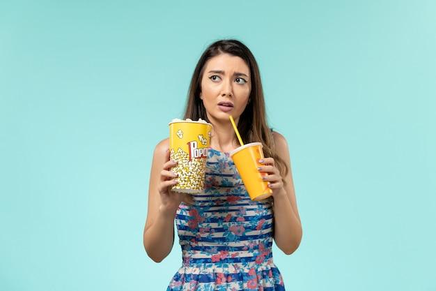 Vista frontale giovane femmina che tiene popcorn drink e guardare film sulla superficie blu