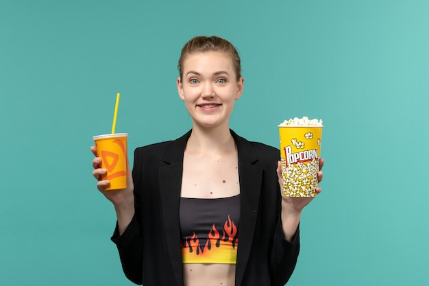 Front view young female holding popcorn drink and watching movie on blue surface