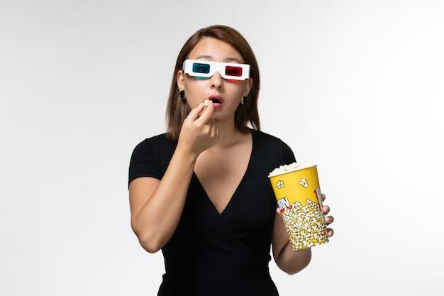 Vista frontale giovane femmina che tiene popcorn e mangiare in occhiali da sole d guardando film su superficie bianca