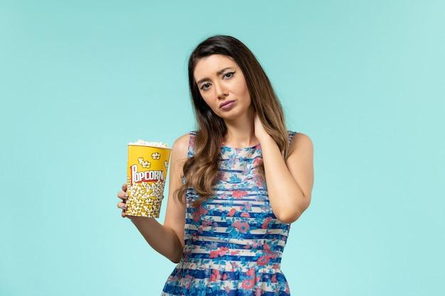 Vista frontale giovane femmina che tiene popcorn e avendo mal di collo sulla superficie blu