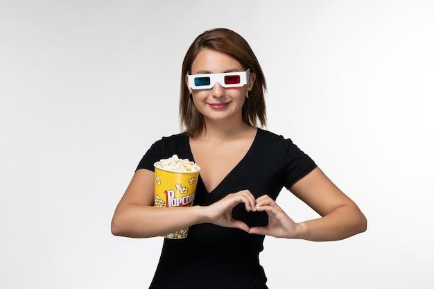 ライトホワイトの表面で映画を見ているdサングラスでポップコーンを保持している正面図若い女性