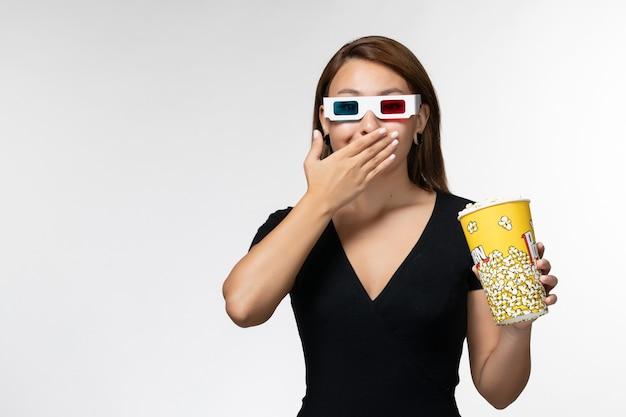 Вид спереди молодая женщина, держащая попкорн в солнцезащитных очках d, смотрит фильм на белой поверхности