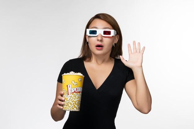 白い表面で映画を見ているdサングラスでポップコーンを保持している正面図若い女性