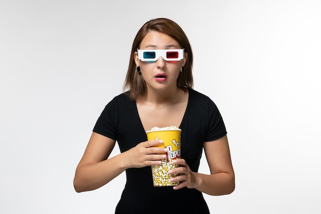 白い表面に注意を払って映画を見ているdサングラスでポップコーンを保持している正面図若い女性