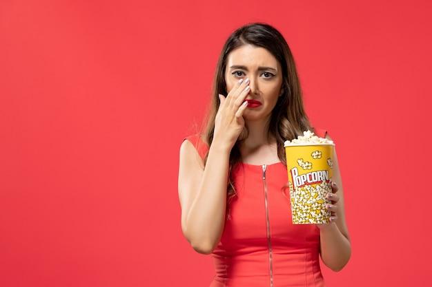 Vista frontale giovane femmina che tiene pacchetto di popcorn piangere mentre si guarda il film sulla superficie rossa