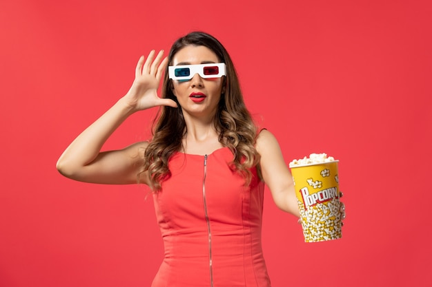 Front view young female holding popcorn package in d sunglasses on light-red surface