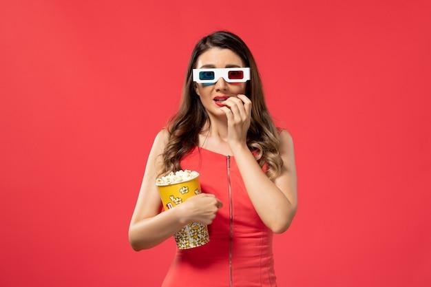 Vista frontale giovane femmina che tiene pacchetto di popcorn in occhiali da sole d sulla superficie rossa