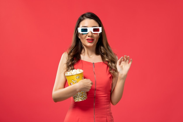 Front view young female holding popcorn package in d sunglasses on the red surface