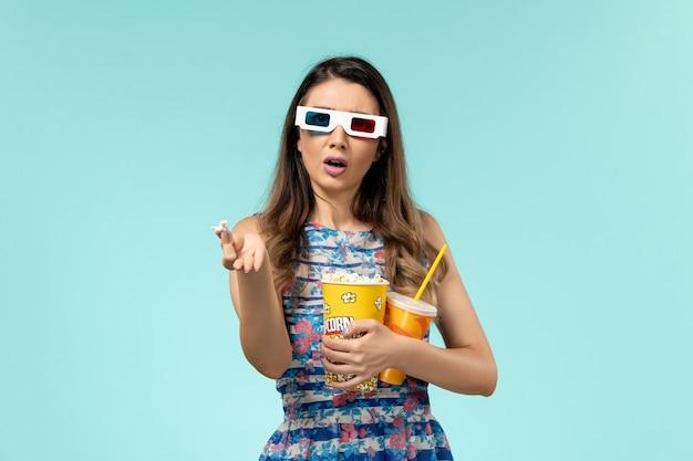 Vista frontale giovane femmina che tiene pacchetto di popcorn e bevanda in occhiali da sole d sulla superficie blu