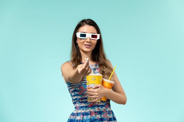 Vista frontale giovane femmina che tiene pacchetto di popcorn e bevanda in occhiali da sole d su superficie azzurra