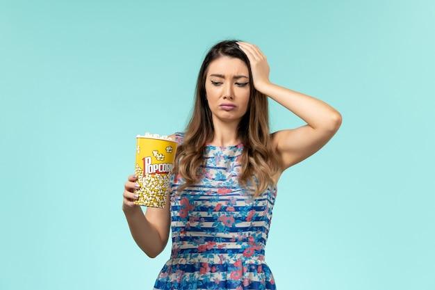 Giovane femmina che tiene pacchetto del popcorn di vista frontale che mangia sulla superficie blu