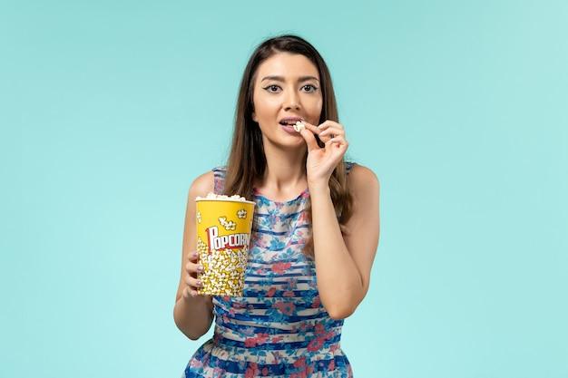 파란색 표면에 먹는 팝콘 패키지를 들고 전면보기 젊은 여성
